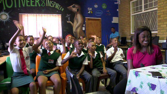 Children in classroom waving
