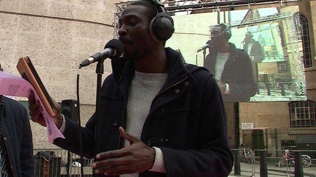 Joshua Idehen reading out a poem on the British-Nigerian diaspora