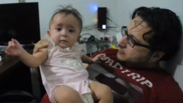 Aleppo doctor Hamza Khatib carrying his daughter.