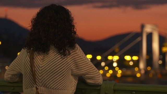 Hungarian woman looking over Budapest at sunset