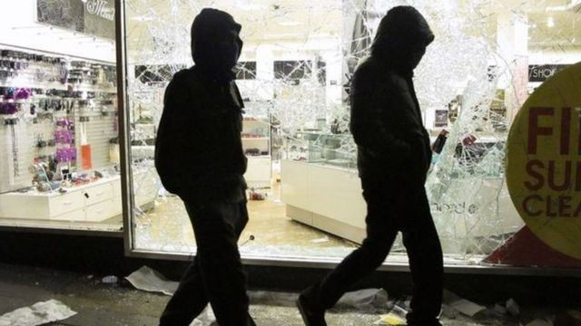 Young men outside looted shop