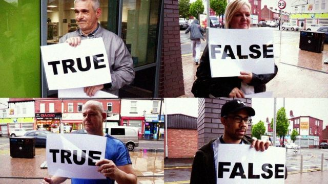 people hold up cards reading true or false