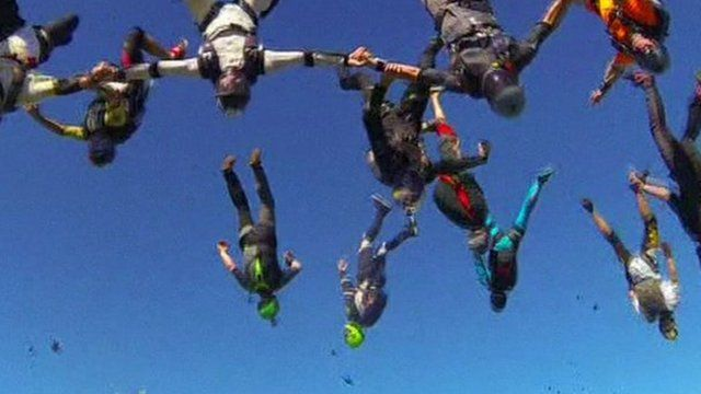 164 skydivers forming the shape of a flower