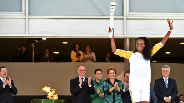 Brazilian volleyball player Fabiana Claudino holds the Olympic torch after receiving it from Brazilian President Dilma Rousseff