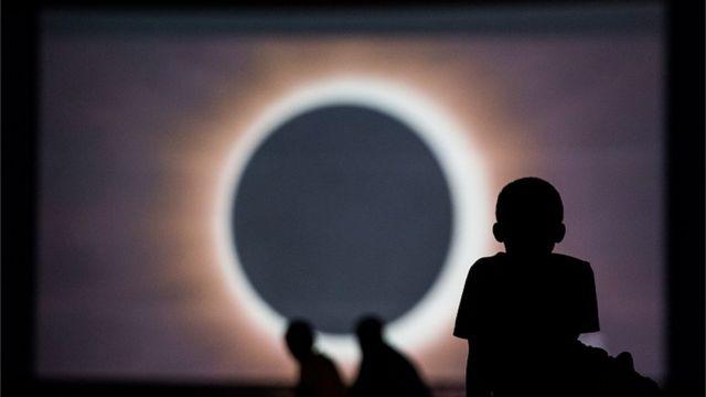 Ребенок смотрит солнечное затмение на экране