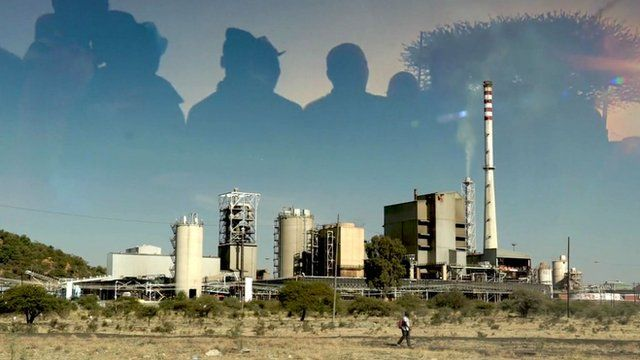 Silhouette of workers over SA platinum mine