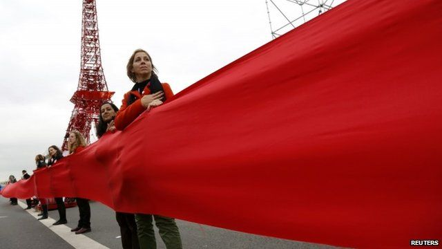 Women take part in a giant red line demonstration as an act of climate disobedience from the COP21 Eiffel Tower replica down the Champs Elysee corridor