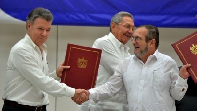 Colombian President Juan Manuel Santos and Farc leader Timochenko shake hands at the ceremony in Havana with Cuban President Raul Castro in the background.