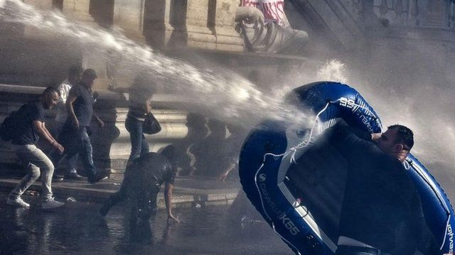Protester uses inflatable boat to shield himself from water cannon in Rome