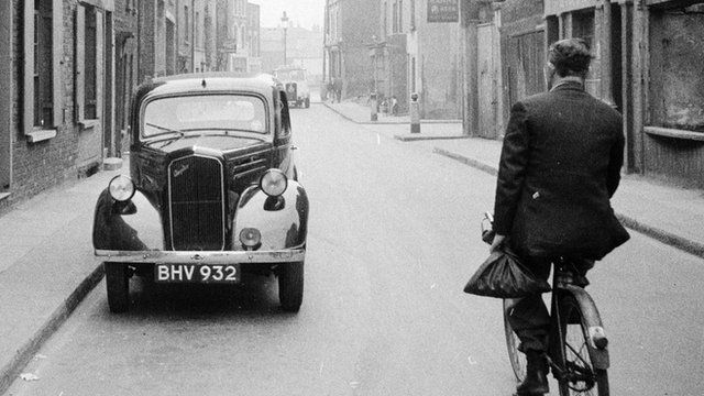 A car and a cyclist in London in the 1950s