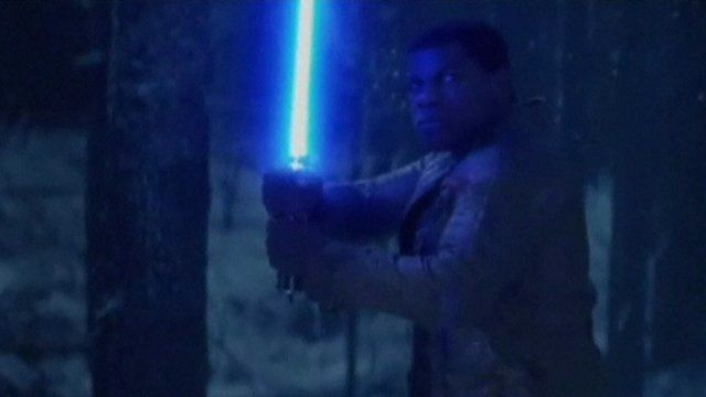 Finn, played by John Boyega, holding a blue lightsaber