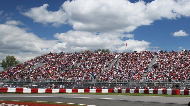 Spectators sit by the F1 track in Montreal. Blue skies and white clouds are overhead.