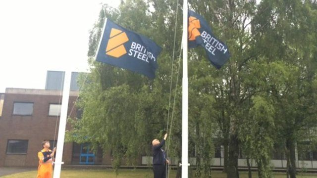 Two men raising two British Steel flags
