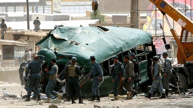 Afghan security forces inspect the site of a bomb attack on the outskirts of Kabul, Afghanistan
