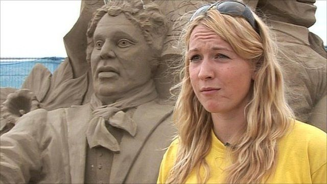 Sand sculptor with example of her work