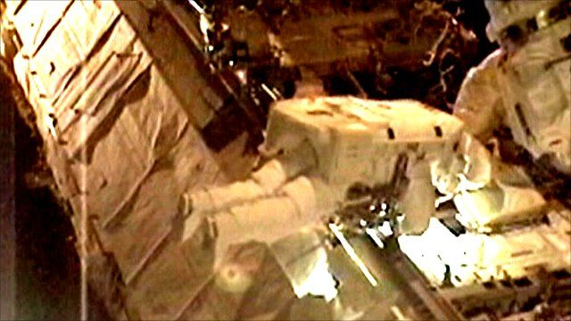 An astronaut attempts to fix the cooling unit on the ISS