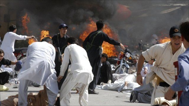 People rush for cover soon after an explosion during a Shiite procession in Quetta