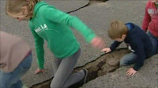 Children walk through crack in road