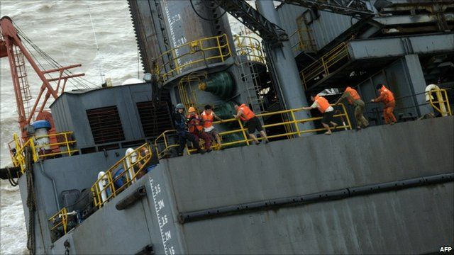 Chinese oil rig workers clinging to side of damaged oil rig