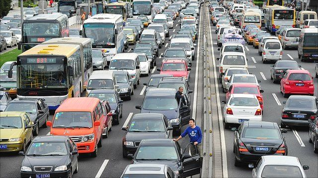 Drivers step out of their vehicles for a better view while stuck in traffic along Beijing's second ring road