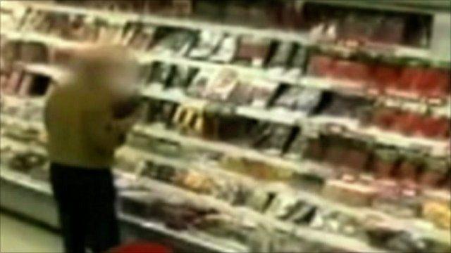 Man stealing food from supermarket cooler