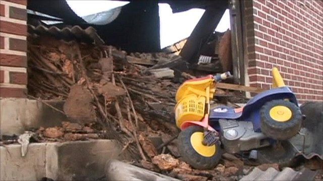 Child's tricycle in wreckage of building