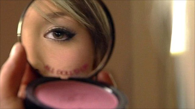 Girl applying make-up in mirror