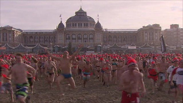 The swimmers run towards the icy waters