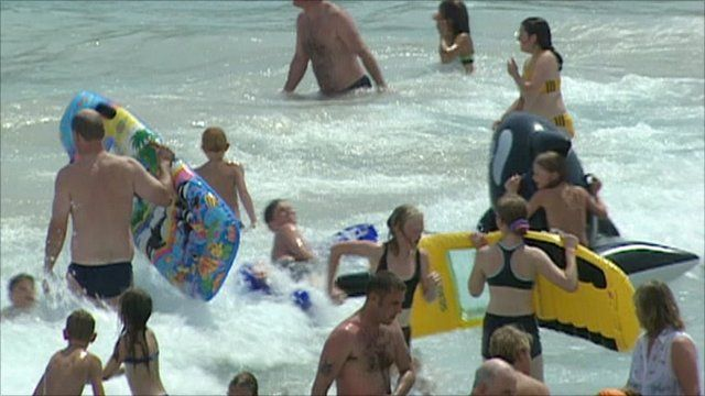 People play in the surf by a beach