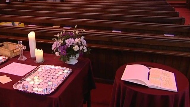 Book of condolence next to candles and flowers