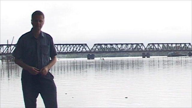 Charles Haviland standing next to flooding in Sri Lanka