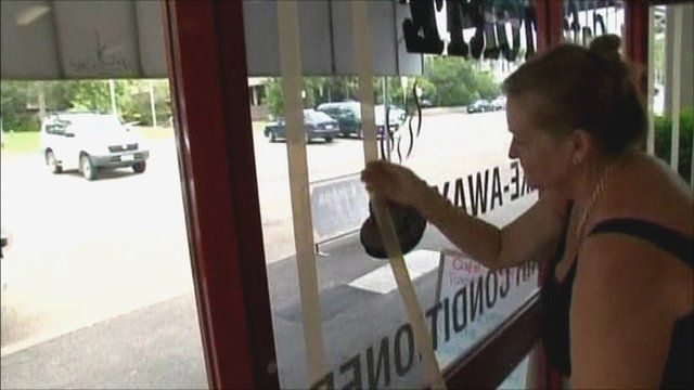 Woman taping up shop windows in Queensland