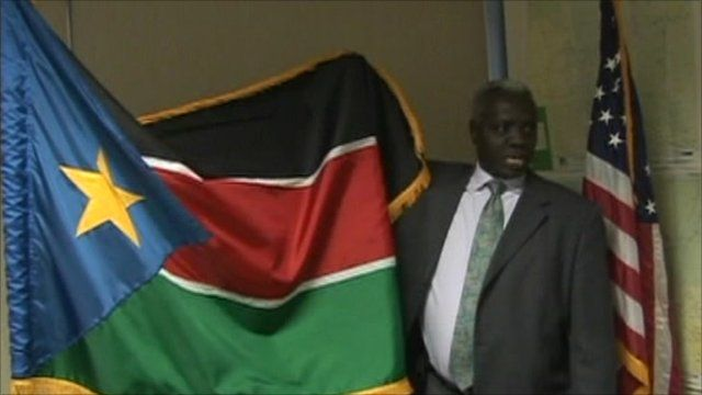 Sudanese man with South Sudan flag and US flag
