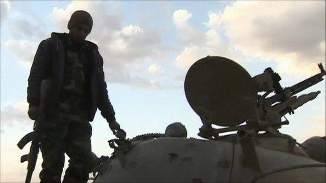 A rebel stands on a tank in Ajdabiya