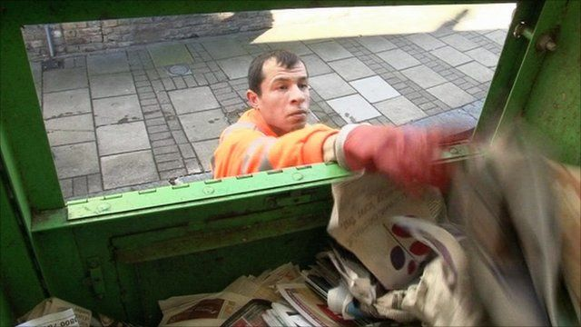 A man puts recycled newspapers into a container
