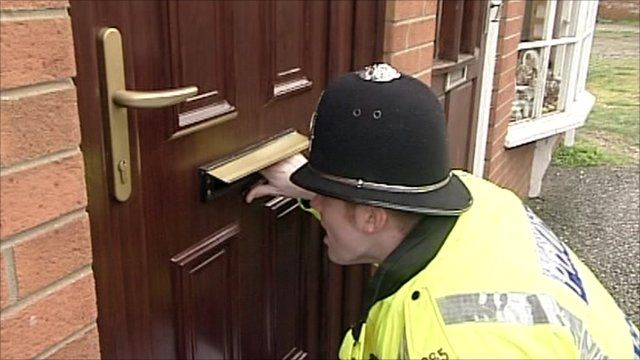 A police officer checks residents have left a house