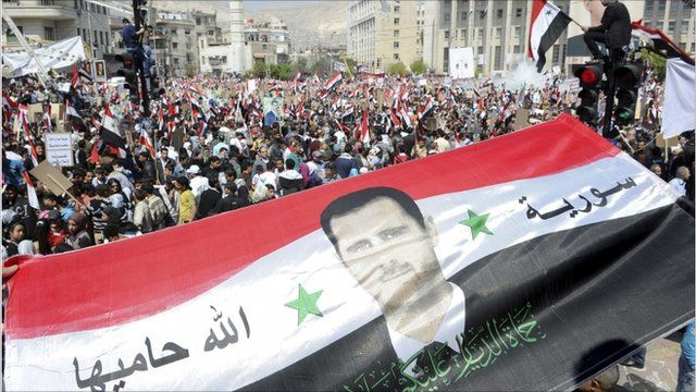 People hold a national flag with a picture of Syria's President Bashar al-Assad during a pro-government rally