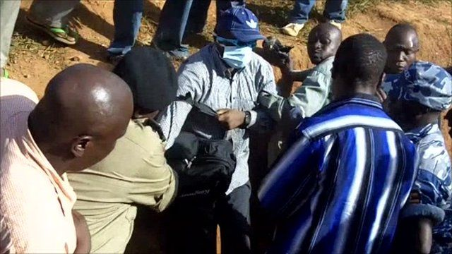 Kizza Besigye (c) surrounded by a group of men