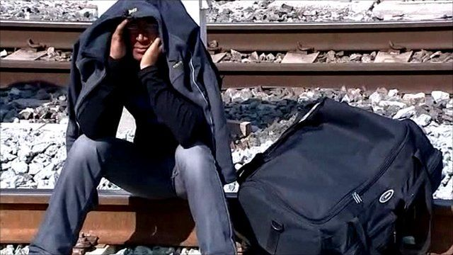 Man sitting on train tracks