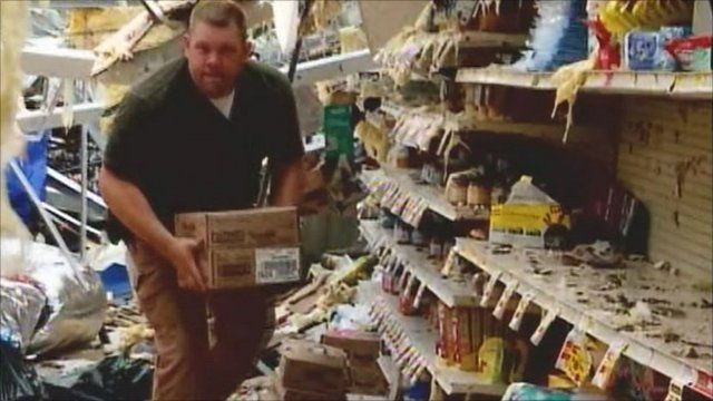 Man moving boxes in his badly damaged shop