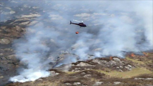 A helicopter drops water on a fire