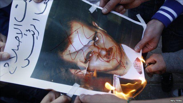 People burning picture of President Bashar al-Assad