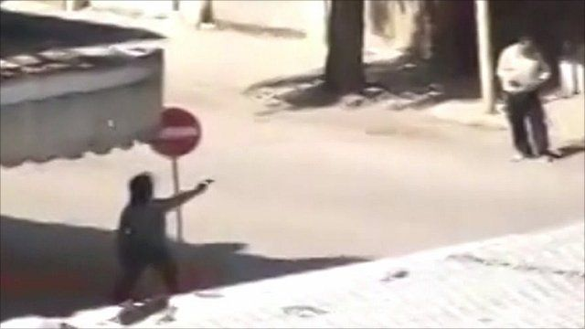 Man shooting a gun on a street in Hama, Syria