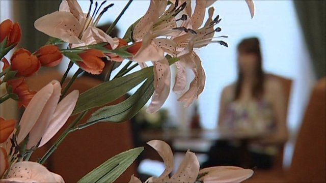 Woman out-of-focus behind flowers