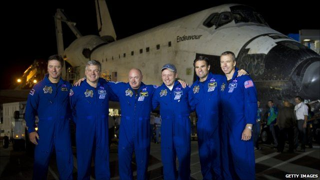 The crew stand in front of shuttle Endeavour