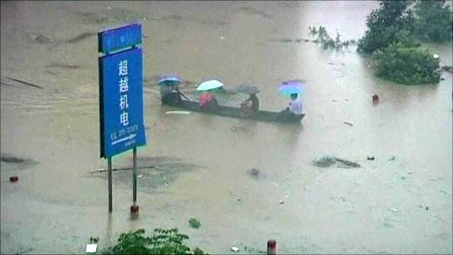 Boat being paddled down a flooded street