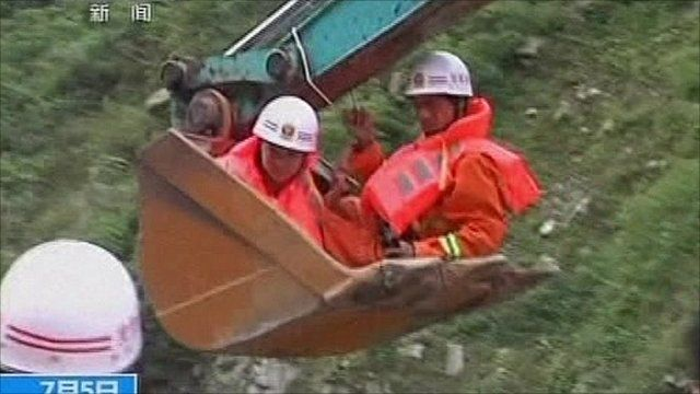 Rescuers in the bucket of a digger