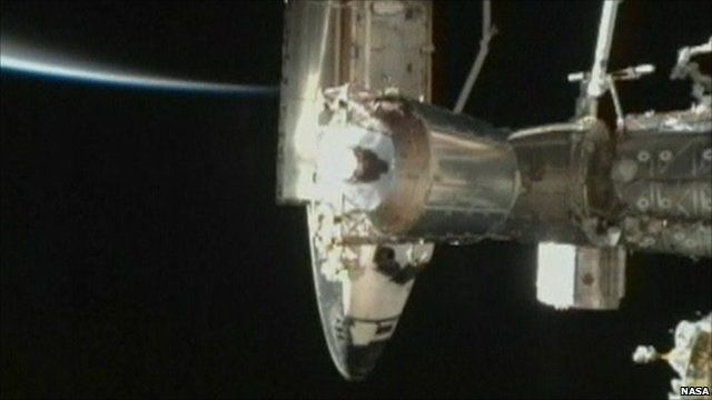 Atlantis docked with the ISS, with Earth in background