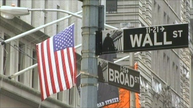 Wall Street and Broad Street signs with a US flag