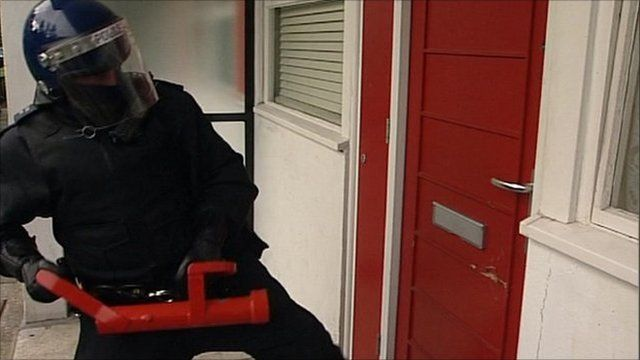 A police officer outside a red door